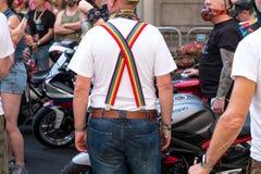 Glad cyklist med hållande övre för för LGBT-regnbågehänglsen/hängslen hans jeans som talar med andra cyklister under bögen Pride  royaltyfri bild
