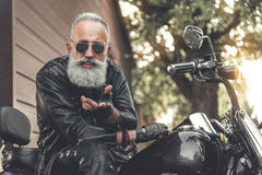 Glad elder male person using motorbike. Cheerful bearded aged biker is sitting on motorcycle and looking at camera with expectation. He offering someone to ride Royalty Free Stock Photo