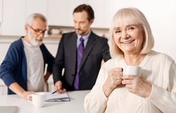 Glad elderly woman relaxing while her husband meeting with lawyer. Taking care about your life. Charming delightful smiling aged women standing and resting while Royalty Free Stock Image