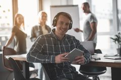 Glad employee resting with music. Portrait of happy men with headphones sitting on chair and holding tablet. His partners standing on background Royalty Free Stock Image