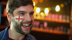 Glad engelsk fotbollsfan med flaggan på kinden som ja gör gesten, segra för lag arkivfilmer