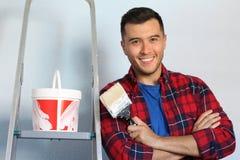 Glad etnisk man omkring som målar väggen fotografering för bildbyråer