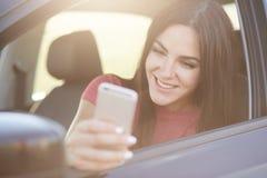 Glad European-het wijfje met lang donker haar, gelukkig om bericht op slimme die telefoon te ontvangen, stelt in auto, ophoudt op royalty-vrije stock afbeelding