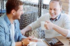 Glad förtjust man och hans farfar som vilar i kafét Royaltyfri Bild