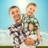 Glad fader med den lycklig sonen som är bekymmerslös och Arkivfoton