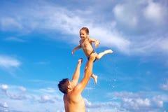 Glad fader och son som har gyckel i vatten på den tropiska stranden Arkivfoto