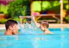 Glad fader och son som har gyckel i waterparkpöl, sommarferier Royaltyfria Foton
