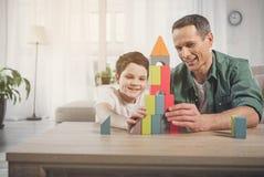 Glad fader och son som konstruerar huset från små detaljer arkivfoto