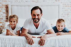 Glad fader och två ungar som lägger på säng royaltyfri foto