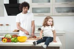 Glad fadermatlagningmat för hans dotter royaltyfria bilder