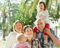 Glad familj av fyra med farmodern som tycker om tid Royaltyfri Bild