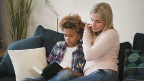 Glad familj läser tillsammans berättelser från bok som håller små barn arkivfilmer