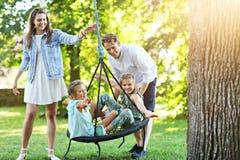 Glad familj som har gyckel på lekplats royaltyfri fotografi