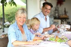 Glad familj som har lunch Arkivfoton