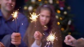 Glad familj som rymmer bengal ljus på jul stock video