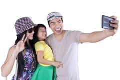 Glad familj som tar bilder i studio Arkivbild