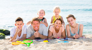 Glad  family with four children lying on beach Stock Photo