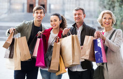 Glad family of four with shopping bags Stock Image