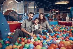 Glad family sitting in pool with balls Royalty Free Stock Photo