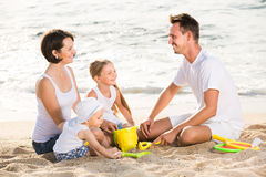 Glad family with two children playing at beach Royalty Free Stock Image