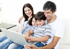 Glad family using a laptop sitting on sofa. At home Royalty Free Stock Images