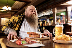 Glad fat male snuffing meal Stock Photography