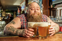 Glad fat man hugging alcohol in bar Royalty Free Stock Images