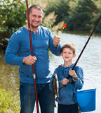 Glad father and son fishing with rods. In summer day Royalty Free Stock Images
