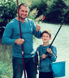 Glad father and son fishing with rods. In summer day Royalty Free Stock Photos