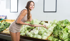 Glad female customer holding fresh cabbage-head Royalty Free Stock Photography