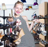 Glad female customer holding many pair of shoes. Glad female customer holding many pair of heeled shoes in fashion store royalty free stock photo