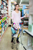 Glad female customer selecting drugstore products. And standing with shopping trolley stock image