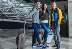 Glad female friends going boarding. Young girls looking aside with joy while standing at the airport hall with baggage. Copy space in left side Stock Image