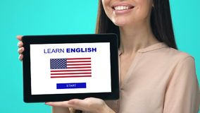 Glad female holding tablet with learn English app, USA flag on screen, education. Stock footage stock footage