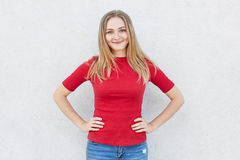 Glad female with light hair and blue eyes having smile on her face wearing red sweater and jeans holding hands on waist. Attracriv Royalty Free Stock Photo