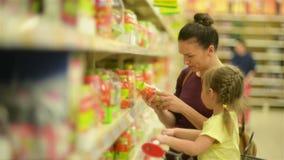 Glad Female Shopper con la figlia che cerca le bevande in supermercato video d archivio