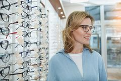 Glad female standing in glasses shop. Side view happy young woman in glasses situating in optical store. Optics concept Stock Photos