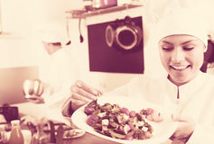 Glad female young cook holding plate. Glad female young cook wearing uniform holding plate with green salad Royalty Free Stock Photo