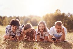 Glad females and their cheerful boyfriends spend free time together outside, hold cell phones in hands, share music files and phot stock images