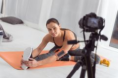 Glad fit blogger doing exercises for her blog. Being healthy. Attractive alert muscular dark-haired young blogger smiling and stretching while sitting on the royalty free stock images