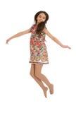 Glad flicka i färgrika klänninghopp Arkivfoto