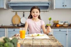 Glad flicka och ha den sunda frukosten Royaltyfria Foton