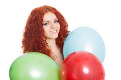 Glad flicka som rymmer färgrika ballonger. royaltyfri foto