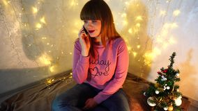 Glad flicka som skvallrar med vännen vid telefonen stock video