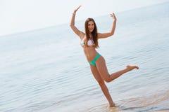 Glad flickadans på stranden arkivfoto