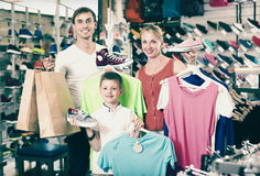 Glad friendly parents with boy in sport store. Glad friendly parents with boy in school age shopping clothing in sport store Royalty Free Stock Photo
