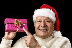 Glad gamal man som pekar på den magentafärgade slågna in gåvan Arkivbild