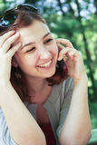 Glad girl. Talking on the phone on nature royalty free stock photos