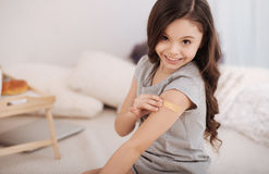 Glad girl applying medical patch on the arm at home Stock Images