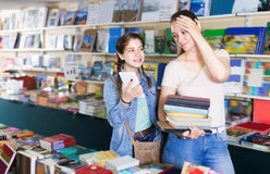 Glad girl chatting on screen tablet and choosing literature book Stock Image